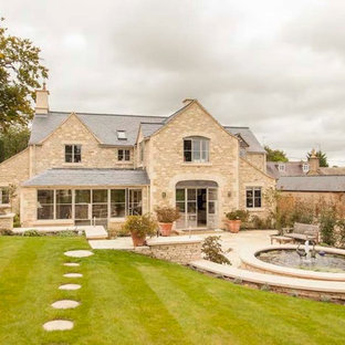 Beige farmhouse two floor exterior in Gloucestershire with stone cladding and a pitched roof.