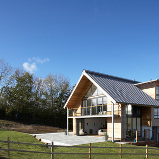 Large and brown rustic split-level exterior in Dorset with wood cladding and a pitched roof.