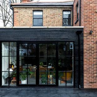 Идея дизайна: двухэтажный, кирпичный, красный дуплекс среднего размера в современном стиле