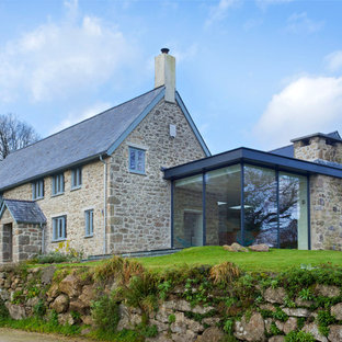 This is an example of a rural two floor exterior in London with stone cladding and a pitched roof.
