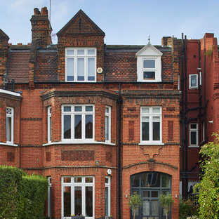 This is an example of a red traditional brick terraced house in London with three floors and a pitched roof.
