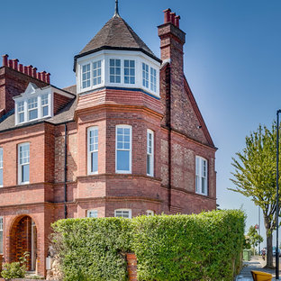Red traditional brick terraced house in London with three floors, a pitched roof and a shingle roof.