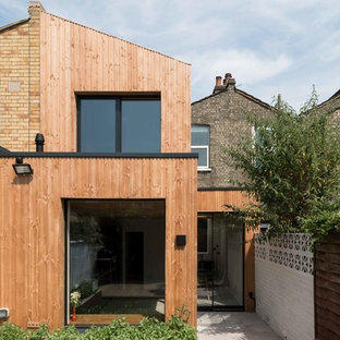 Photo of a medium sized contemporary two floor terraced house in London with wood cladding and a lean-to roof.