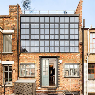 Example Of A Trendy Two Story Brick Flat Roof Design In London