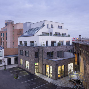 Photo of a small and gey contemporary brick exterior in London with three or more floors and a flat roof.