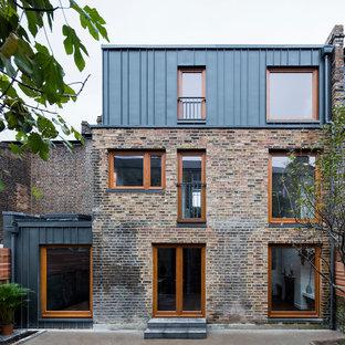 Imagen de fachada de casa pareada multicolor, contemporánea, grande, a niveles, con revestimientos combinados, tejado a la holandesa y tejado de metal