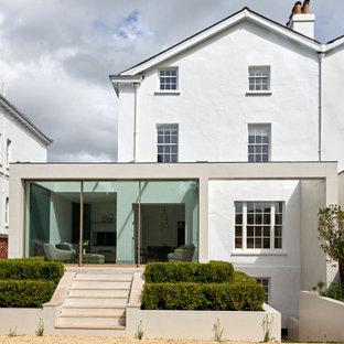 Cette image montre une façade de maison double beige minimaliste de taille moyenne et à trois étages et plus avec un revêtement mixte, un toit plat et un toit mixte.