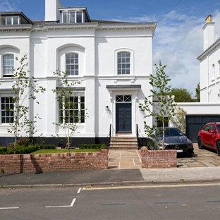 Inspiration pour une façade de maison double blanche traditionnelle de taille moyenne et à trois étages et plus avec un revêtement en stuc, un toit à quatre pans et un toit en tuile.