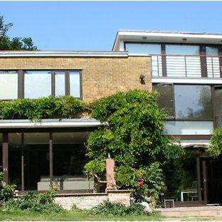 Modelo de fachada de casa beige, retro, grande, a niveles, con revestimiento de ladrillo, tejado plano y tejado de varios materiales
