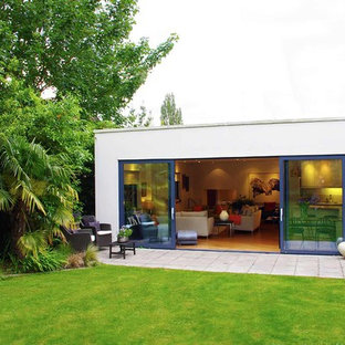 Expansive and white modern one floor glass house exterior in London with a flat roof.