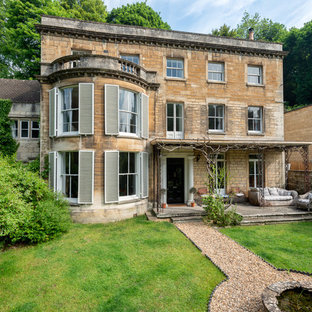 This is an example of a large and beige victorian two floor detached house in Gloucestershire with stone cladding, a tiled roof and a flat roof.
