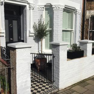 На фото: двухэтажный, кирпичный, белый дом среднего размера в стиле неоклассика (современная классика) с двускатной крышей с