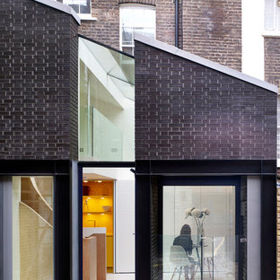 Small trendy black split-level brick gable roof photo in London with a metal roof