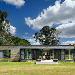 This is an example of a medium sized contemporary one floor exterior in Hampshire with wood cladding and a flat roof.