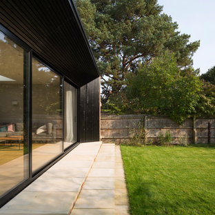 Mid-sized minimalist black two-story wood exterior home photo in Cambridgeshire with a metal roof