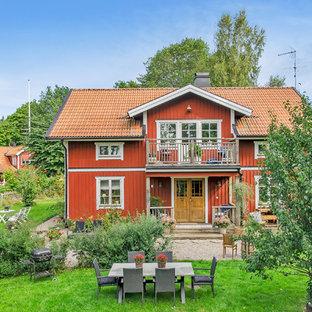 Inspiration för mellanstora lantliga röda trähus, med två våningar och sadeltak