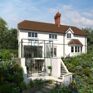 Inspiration for a beige contemporary render exterior in Surrey with three or more floors and a pitched roof.