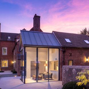 Foto della facciata di una casa unifamiliare grande contemporanea a tre o più piani con rivestimento in metallo, tetto a capanna e copertura in metallo o lamiera