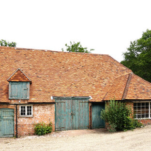 This is an example of a red country one floor brick detached house in London with a hip roof and a shingle roof.