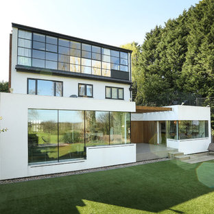Multi-coloured and large modern brick detached house in London with a flat roof, a green roof and three floors.