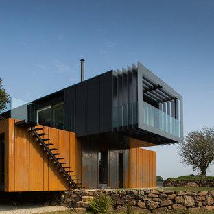 Immagine della facciata di una casa contemporanea a due piani con rivestimento in metallo e tetto piano