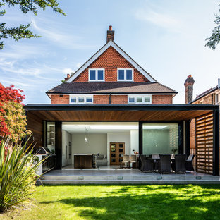 Design ideas for a medium sized and red contemporary two floor detached house in Surrey with mixed cladding, a pitched roof and a shingle roof.