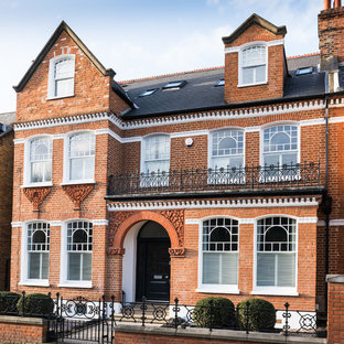 Red and expansive victorian brick semi-detached house in London with a pitched roof and three floors.