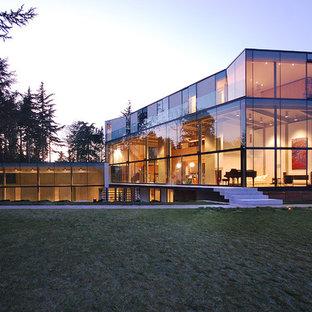Modern inredning av ett stort vitt hus, med tre eller fler plan, glasfasad och platt tak