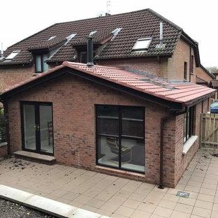 Modelo de fachada de casa bifamiliar contemporánea con revestimiento de ladrillo y tejado a doble faldón