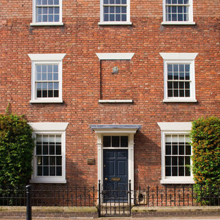 This is an example of a red classic brick terraced house in Other with three or more floors and a flat roof.