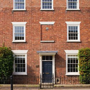 Foto de fachada de casa pareada roja, tradicional, de tres plantas, con revestimiento de ladrillo y tejado plano