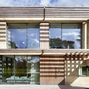 Beige contemporary two floor detached house in Surrey with a flat roof and mixed cladding.