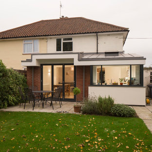 Inspiration for a mid-sized modern white two-story stucco duplex exterior remodel in Cambridgeshire with a metal roof