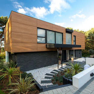Inspiration for a medium sized and black contemporary two floor detached house in Dorset with wood cladding and a flat roof.