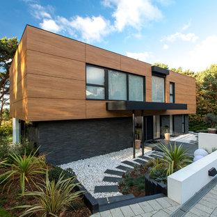 Ejemplo de fachada de casa negra, contemporánea, de tamaño medio, de dos plantas, con revestimiento de madera y tejado plano