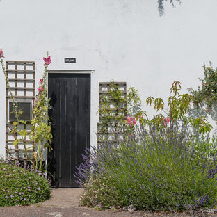 Small eclectic white two-story stucco exterior home photo in Devon