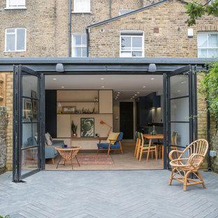 Ispirazione per la facciata di una casa a schiera beige contemporanea a tre o più piani con rivestimento in mattoni