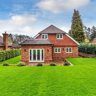 Photo of a red and large classic two floor brick detached house in Surrey with a pitched roof.