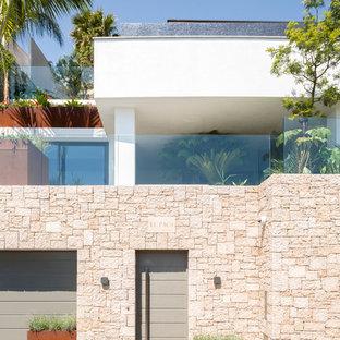 Réalisation d'une façade en pierre blanche design de taille moyenne et à deux étages et plus avec un toit plat.