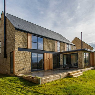 Photo of a brown traditional two floor brick detached house in Sussex with a pitched roof and a shingle roof.