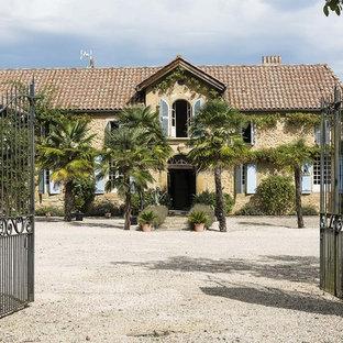 Cette photo montre une grande façade de maison beige méditerranéenne à un étage avec un toit à quatre pans.