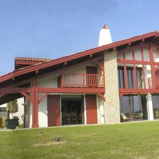 Idée de décoration pour une grande façade de maison blanche design de plain-pied avec un toit à deux pans et un toit en tuile.