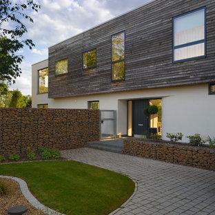 Diseño de fachada blanca, contemporánea, de dos plantas, con revestimiento de madera