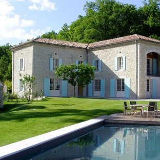 Photo of a mediterranean two floor exterior in Other with stone cladding and a hip roof.