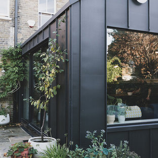 Inspiration for a mid-sized contemporary black one-story metal exterior home remodel in London with a metal roof