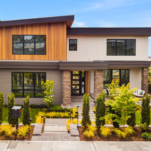 Imagen de fachada de casa multicolor, retro, de dos plantas, con revestimientos combinados y tejado de un solo tendido