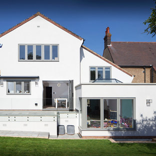 Large traditional white three-story stucco gable roof idea in Hertfordshire