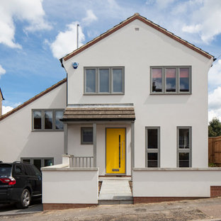Large contemporary white two-story stucco gable roof idea in Hertfordshire