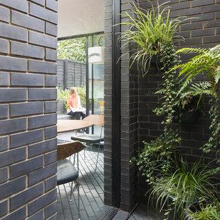 Ispirazione per la facciata di una casa a schiera nera contemporanea a un piano con rivestimento in mattoni, tetto piano e copertura mista