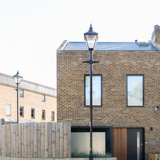 Brown contemporary two floor brick exterior in London with a pitched roof.